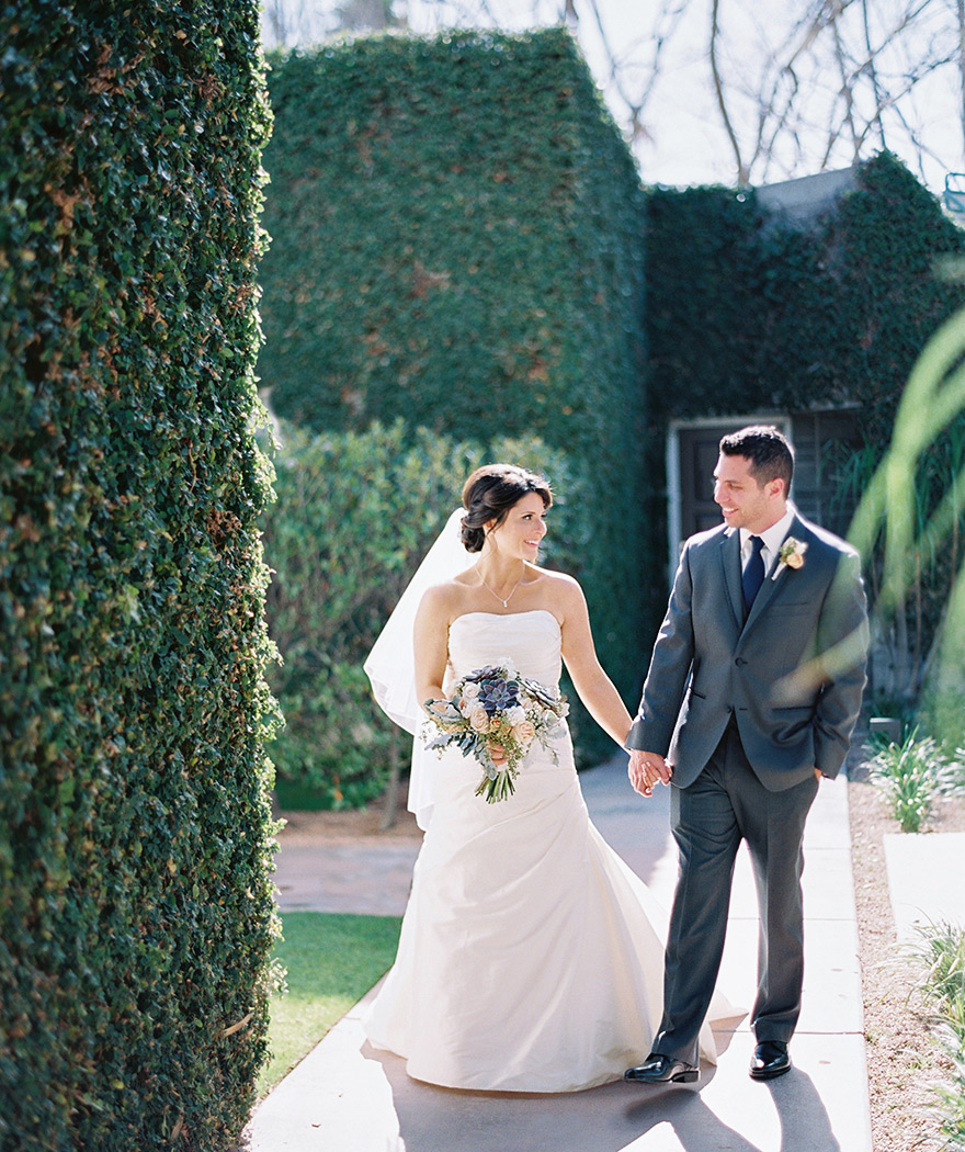 bride & groom hold hands in front of an ivy-covered wall