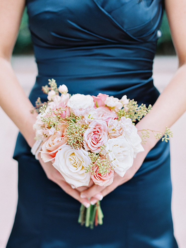 bridesmaid in midnight blue satin, pink and peach bouquet