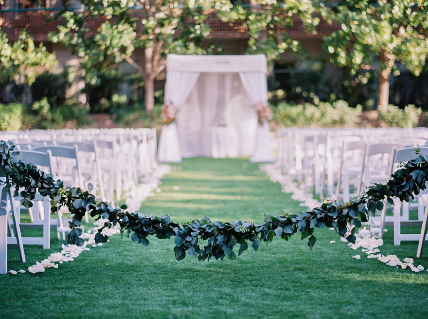 garland drawn across the aisle, outdoor wedding ceremony