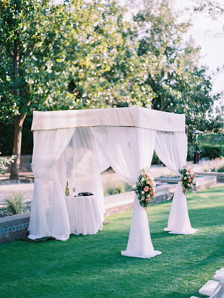 chuppah with fresh flowers, topped by a custom quilt