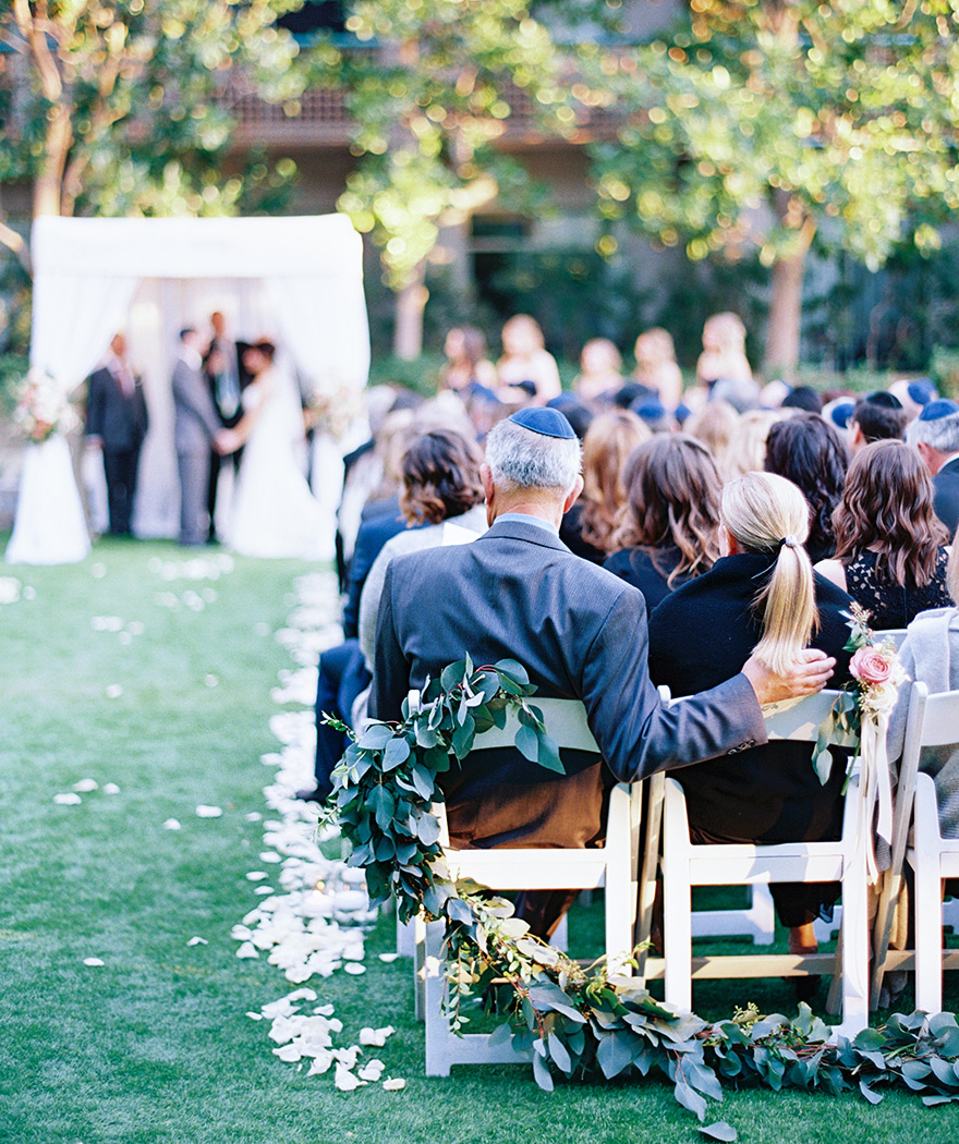 guests watch an outdoor wedding ceremony, chuppah