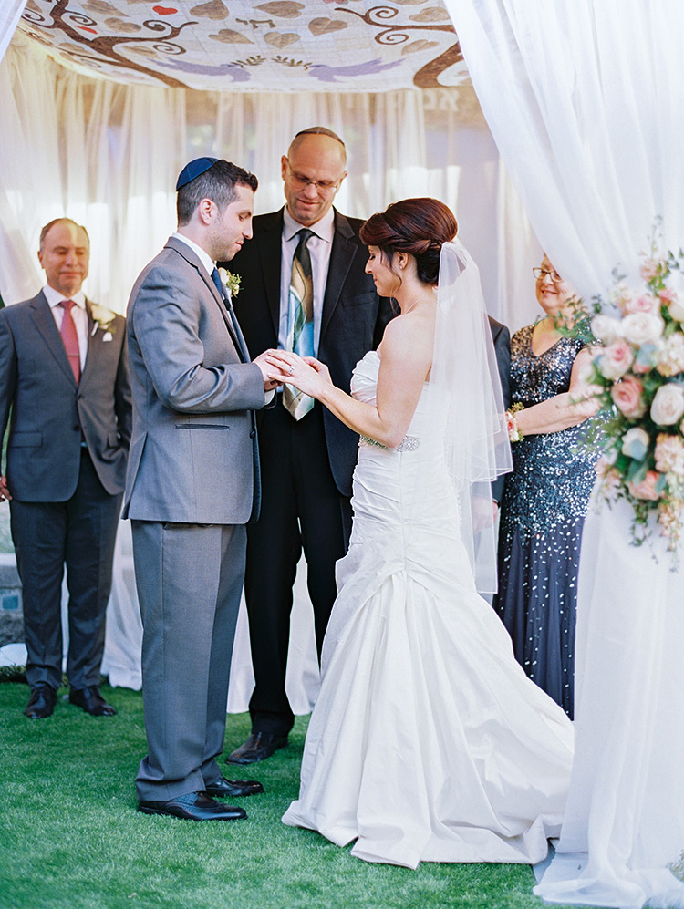 bride & groom exchange rings under the chuppah