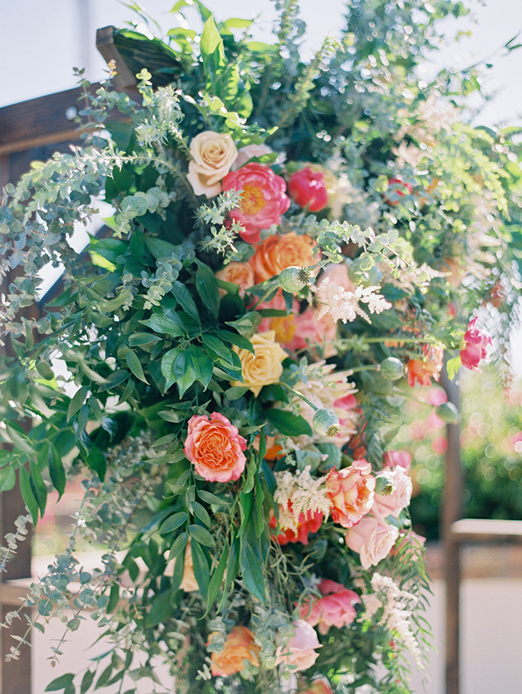 wooden wedding arch with lush spring flowers