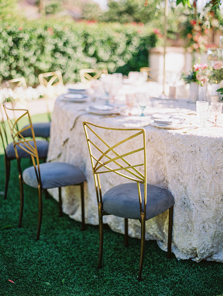 wedding reception with gold fanfare chairs & textured tablecloth