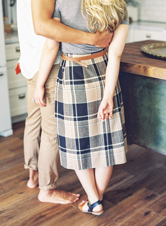 Large-scale plaid skirt & gray tee for her, striped shirt & khakis for him. Kitchen engagement.