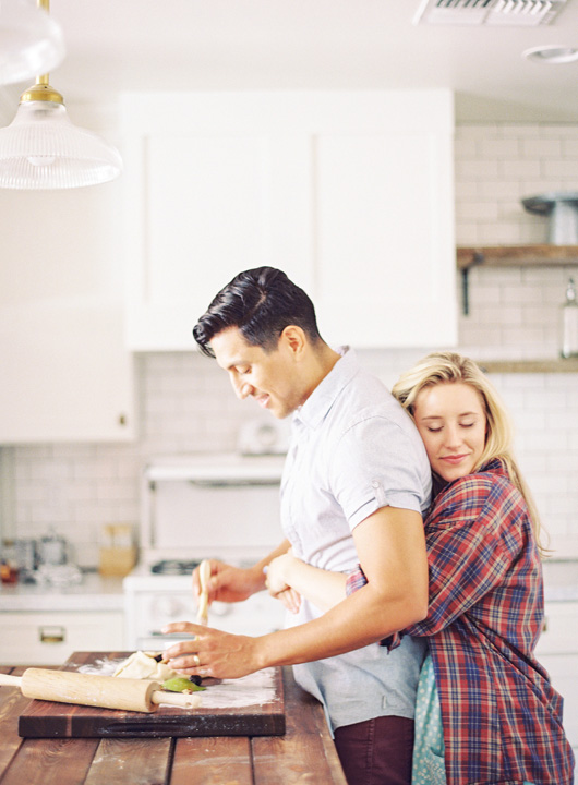 She hugs him from behind as he cooks. Intimate kitchen engagement shoot.