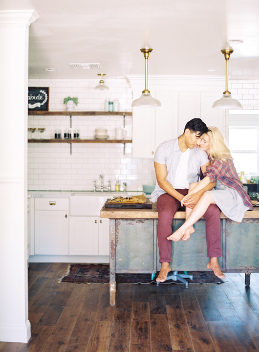 Couple cuddling on a retro kitchen island. Intimate kitchen engagement shoot.