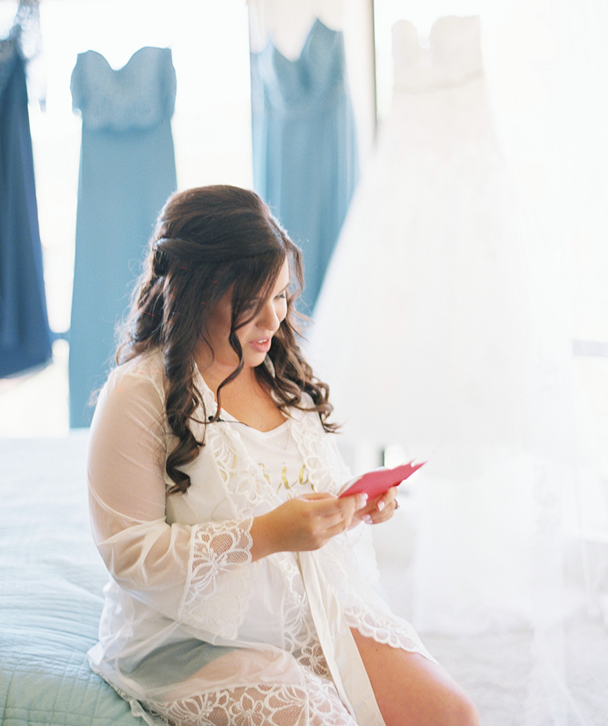 bride getting ready in a pretty lace robe