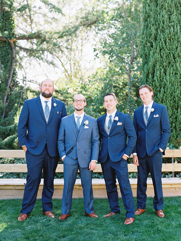 dapper groomsmen in blue three piece suits