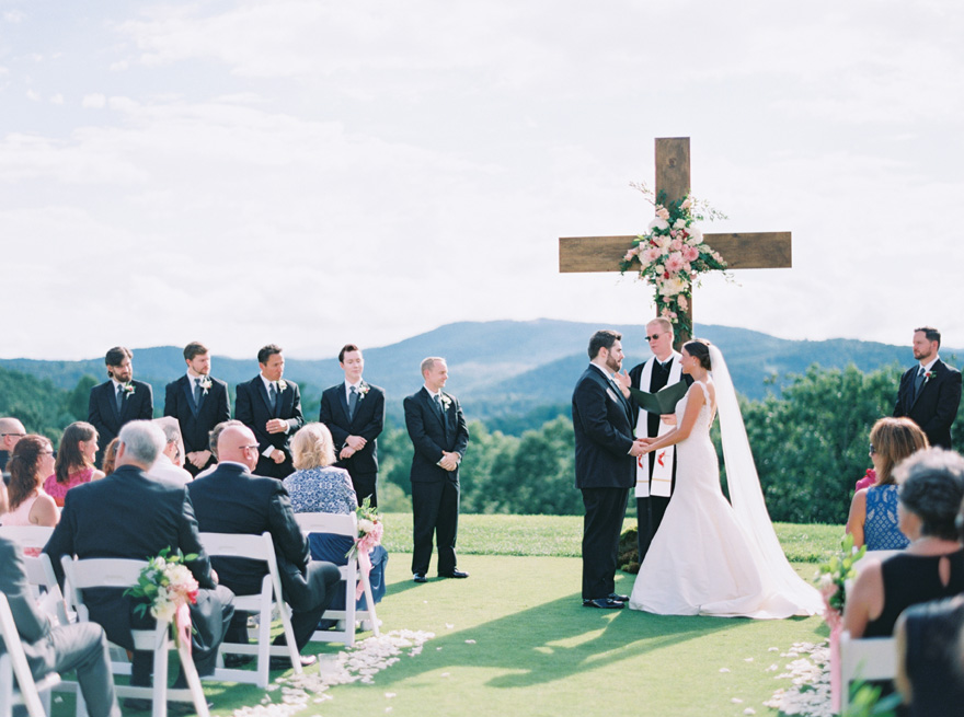 bride & groom recite their vows before a wooden cross