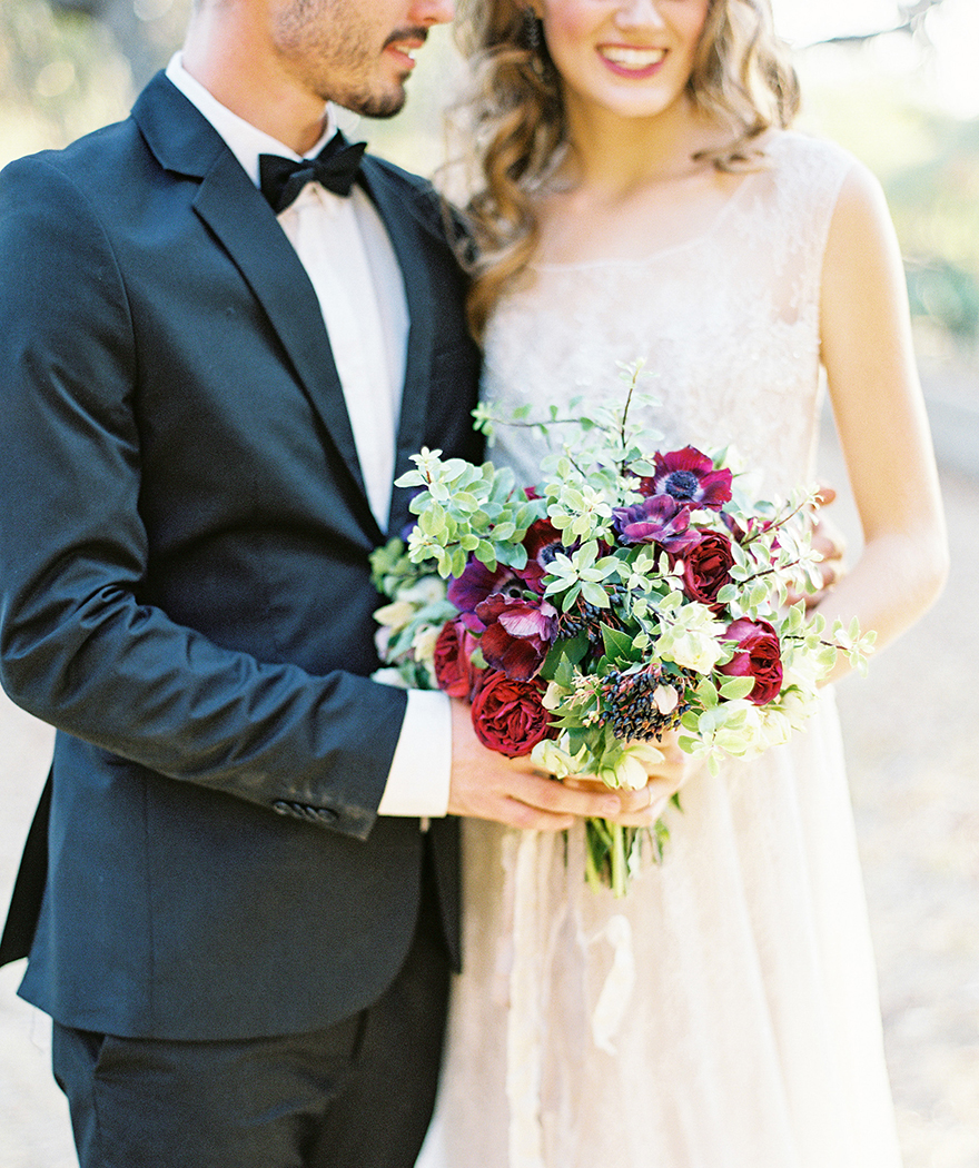 traditional tux for him, beaded gown and romantic red bouquet for her