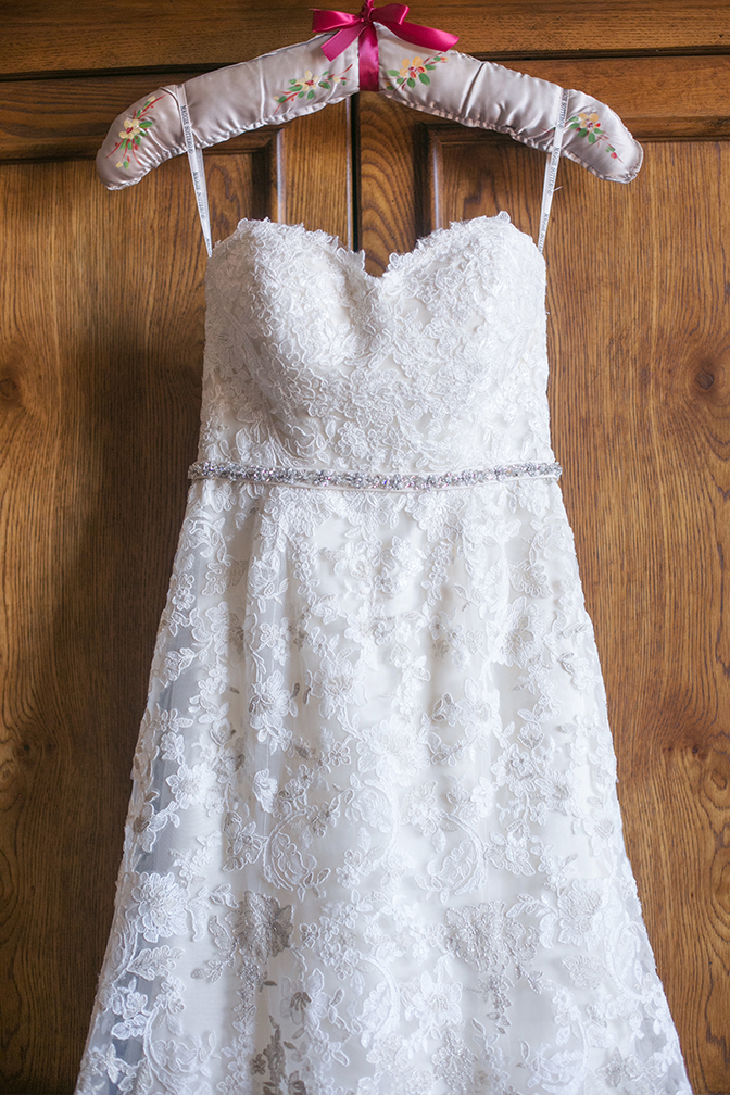 Lace Maggie Sottero gown with a sweetheart neckline hanging on a vintage padded hanger