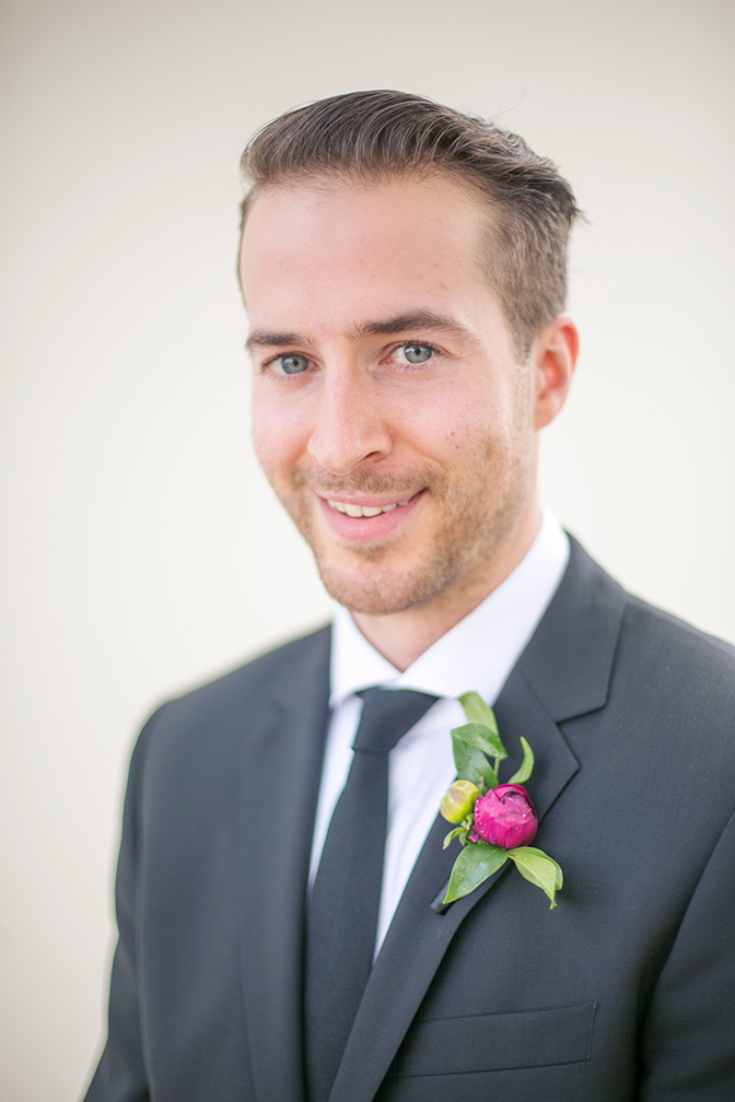 Happy and stylish young groom with a vivid burgundy boutonniere