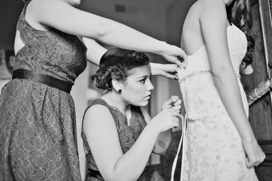 Two bridesmaids help the bride into her dress.