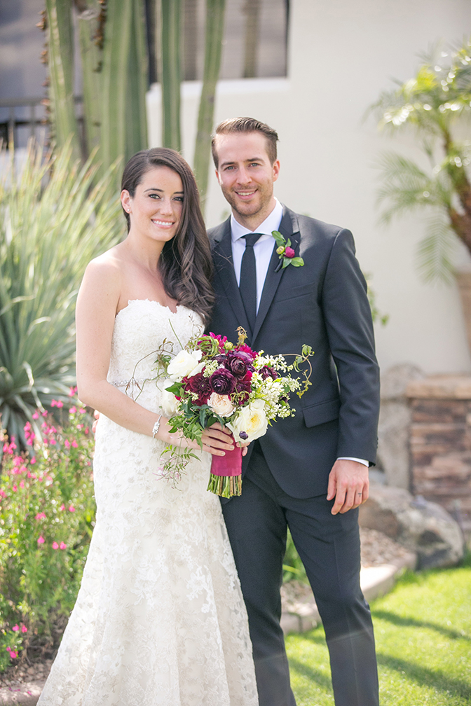 Stylish young bride & groom. Lace wedding gown, lavish bouquet