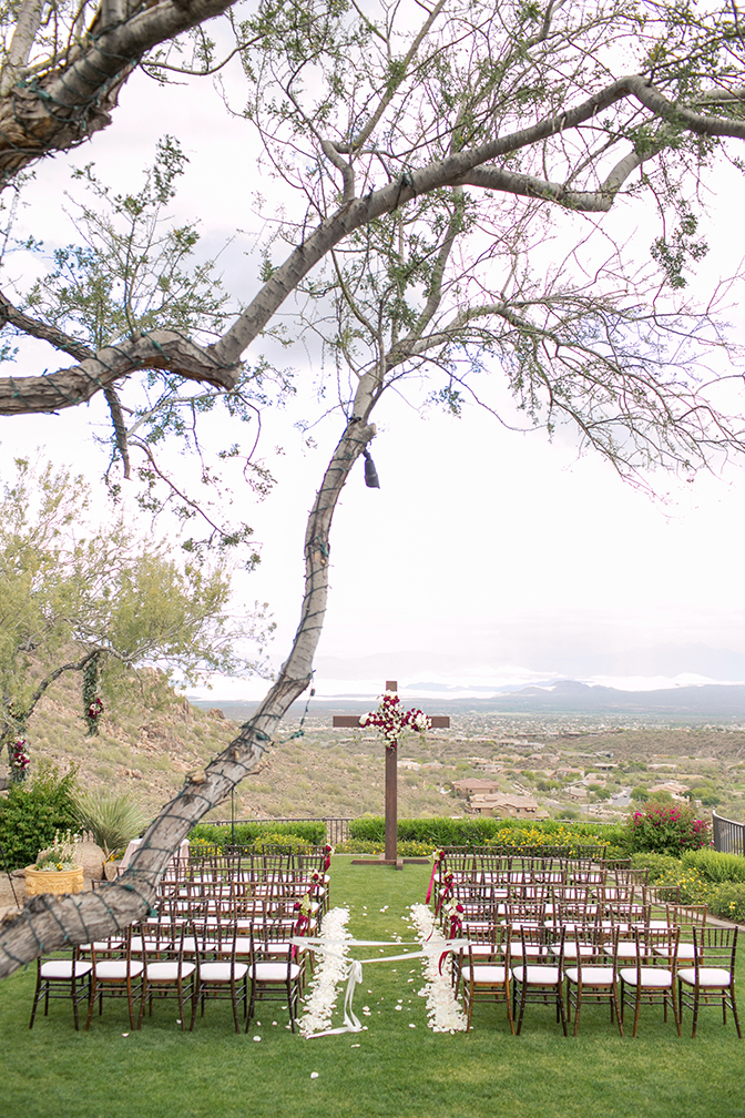 Outdoor wedding ceremony looking out from the McDowell Mountains. Wooden cross dressed in roses.