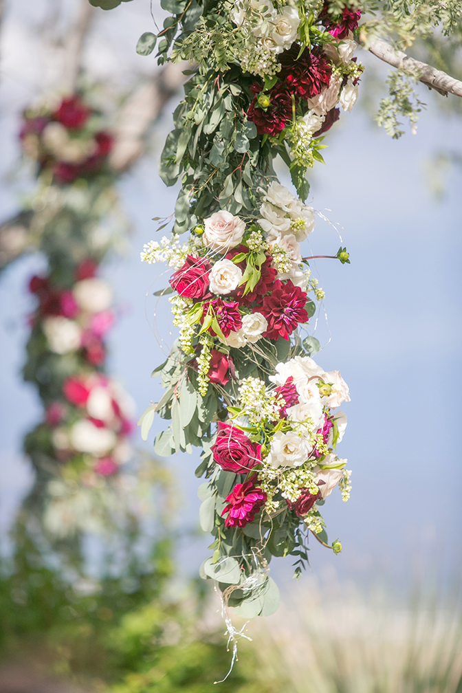 Thick garlands of roses and dahlias with greenery, draped on tree branches. Outdoor wedding flowers