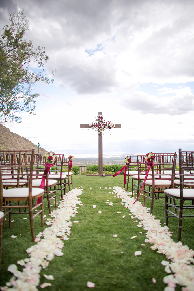 Outdoor wedding ceremony with a large wooden cross decorated with white and burgundy flowers