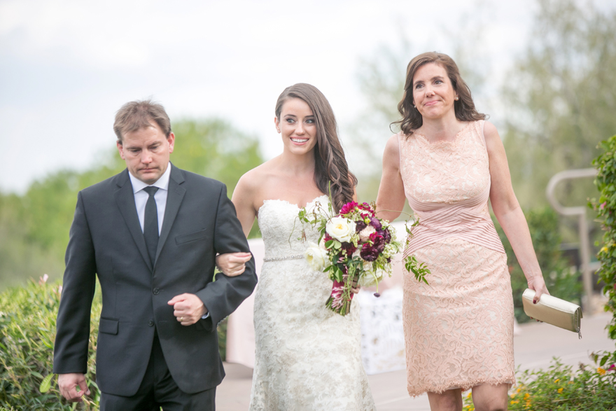 Bride walked down the aisle by her parents. Blush mother-of-the-bride dress. Lace wedding dress.