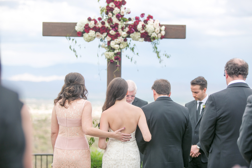 Parents of the bride stand with her to give her away. Outdoor wedding ceremony