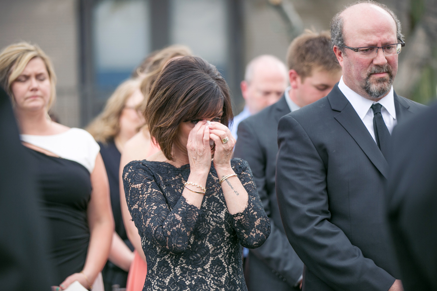 Mother of the groom cries as she watches the wedding. Wedding guests.