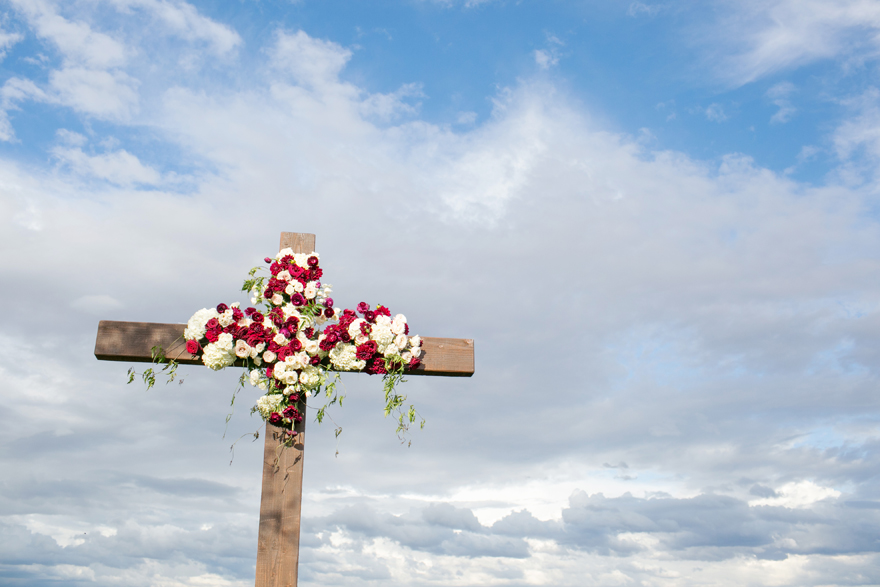 Large wooden cross decorated with white and burgundy flowers against a cloudy sky. Outdoor wedding