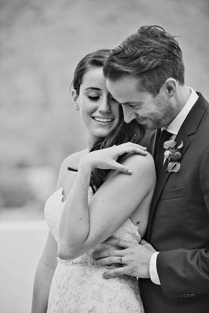 Elegant young bride & groom with small tattoos of each other's first initial.