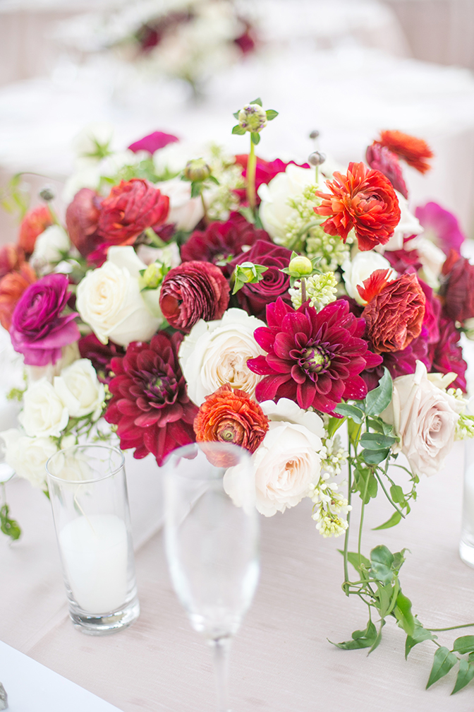 Reception centerpiece in white and wine tones, on a blush table cloth.