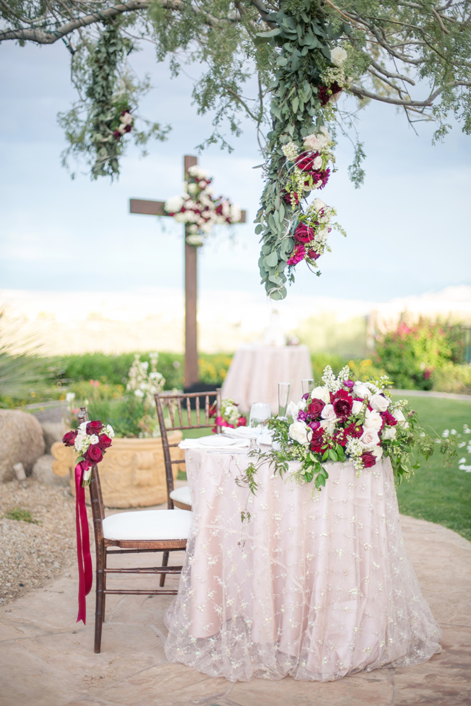 Sweetheart table covered in blush linen and beaded lace. Lavish flowers in white and wine tones