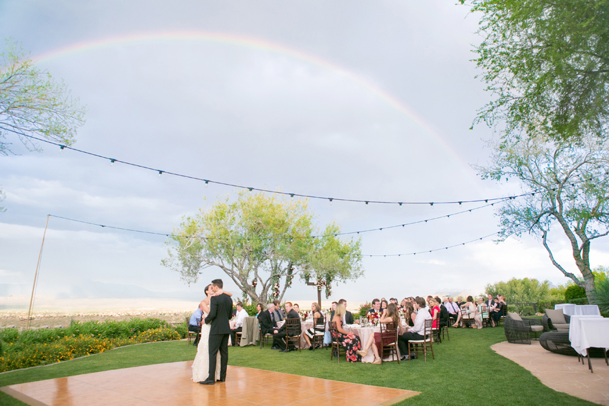 Outdoor wedding reception. First dance with a rainbow overhead