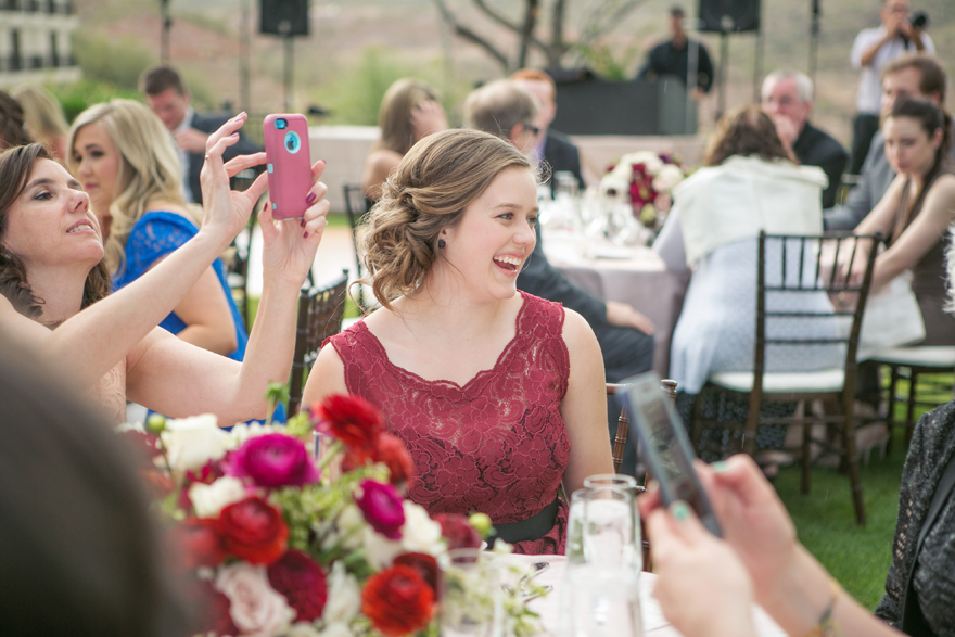 Wedding guests laugh during the outdoor reception