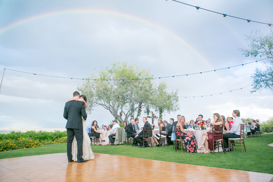 Outdoor wedding reception. First dance with a double rainbow overhead
