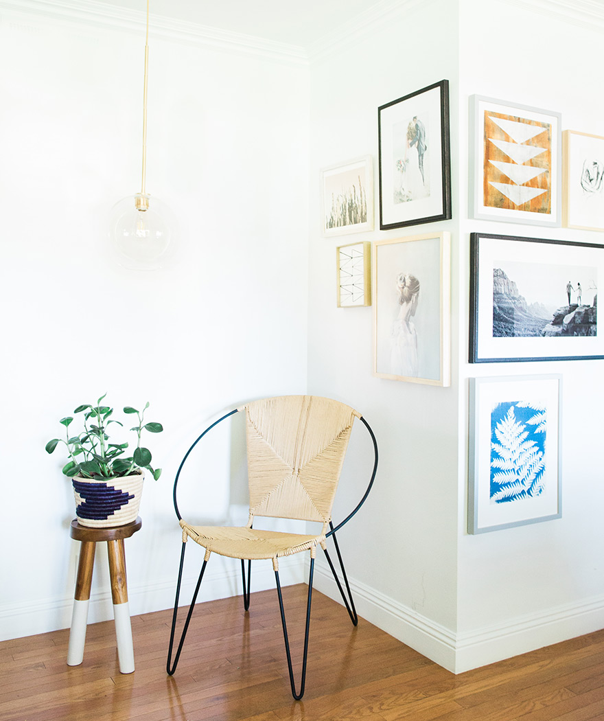 rattan chair and dipped wooden stool near a gallery wall