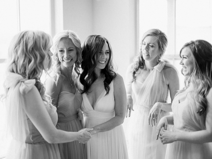 happy bridesmaids in tulle surround the beautiful bride