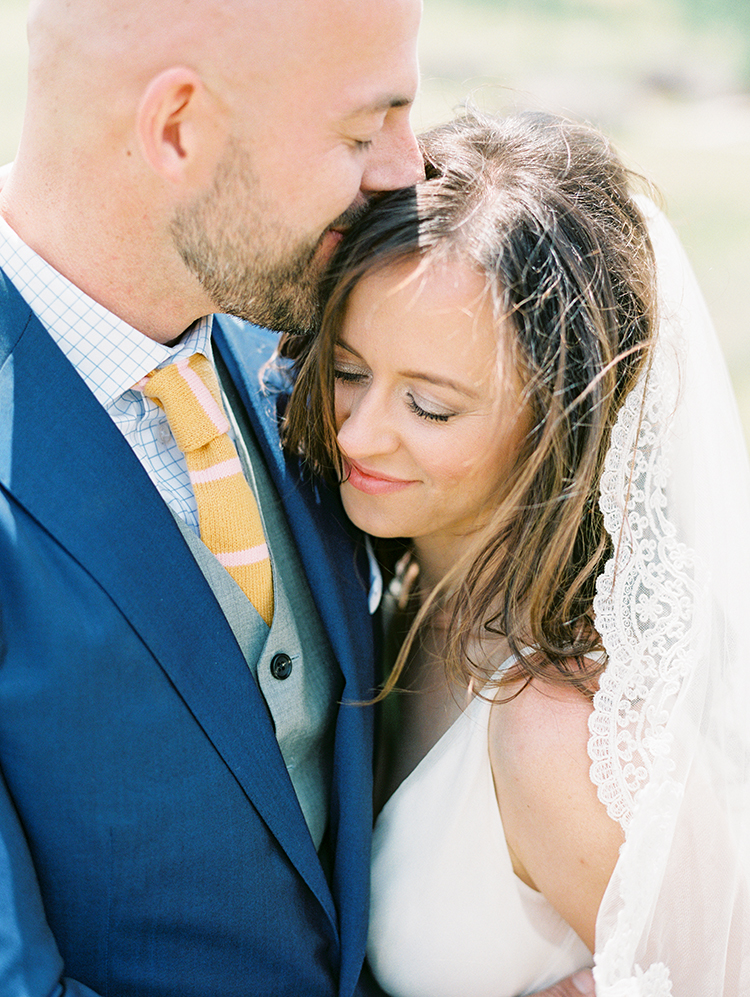 custom suit with knit tie for the groom, scalloped lace veil for the bride