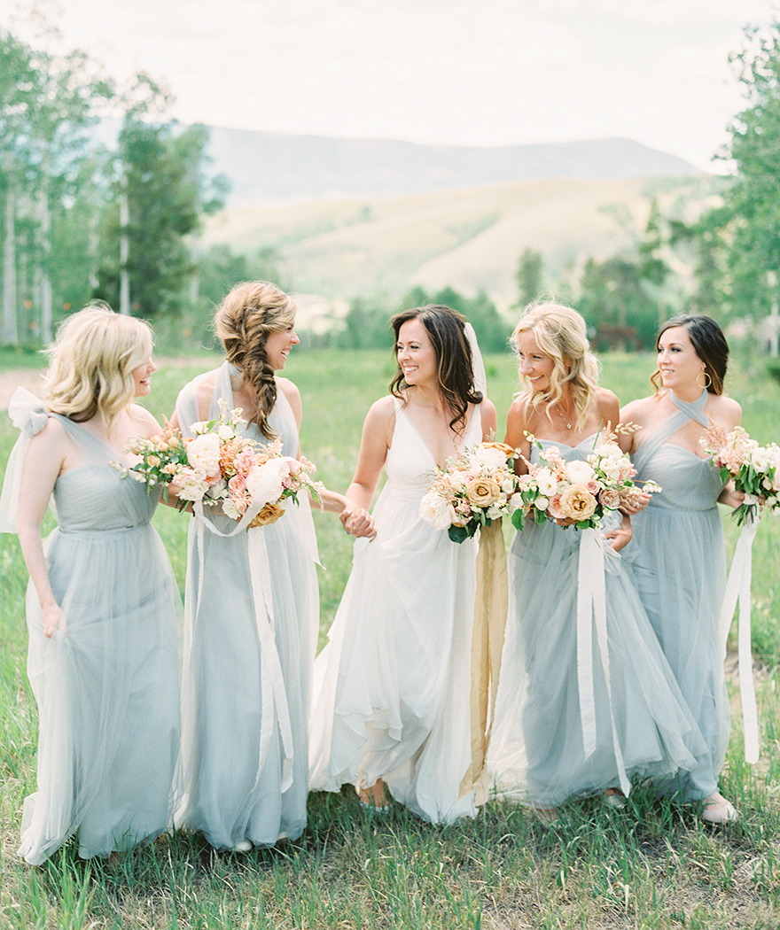 beautiful bridesmaids in grey laugh with the bride