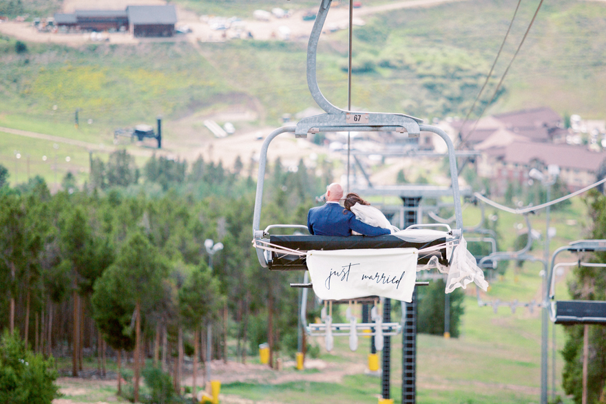 bride & groom descend the mountain on a ski lift