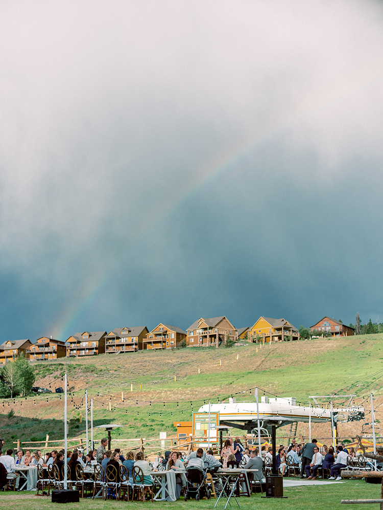 rainbow over an outdoor wedding reception in the mountains