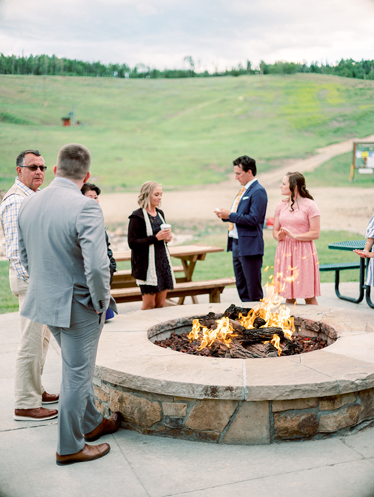 around the fire at an outdoor wedding reception