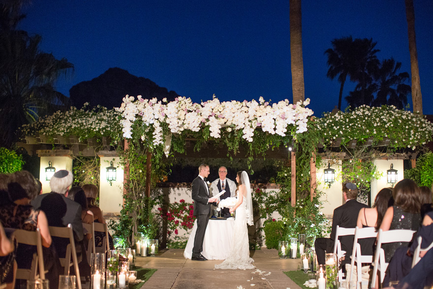 sunset ceremony beneath a flower-decked chuppah