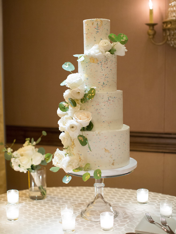 fun four-tiered wedding cake with sprinkles and roses
