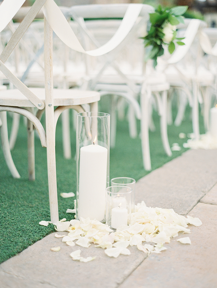 outdoor wedding ceremony decorated with white flowers & candles