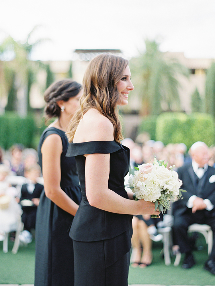 bridesmaid in black with pale flowers