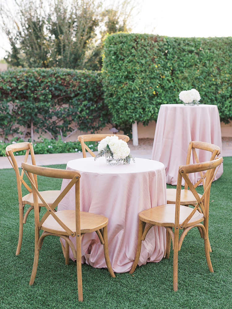 blush linens and white flowers at an outdoor cocktail hour