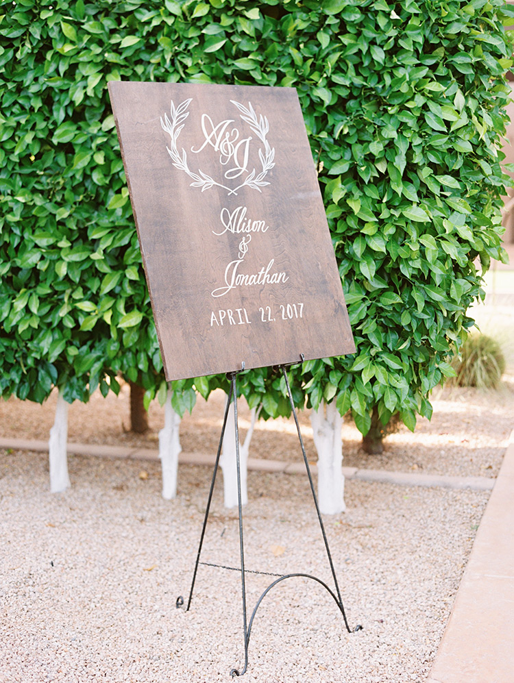 unique wooden sign at an outdoor wedding