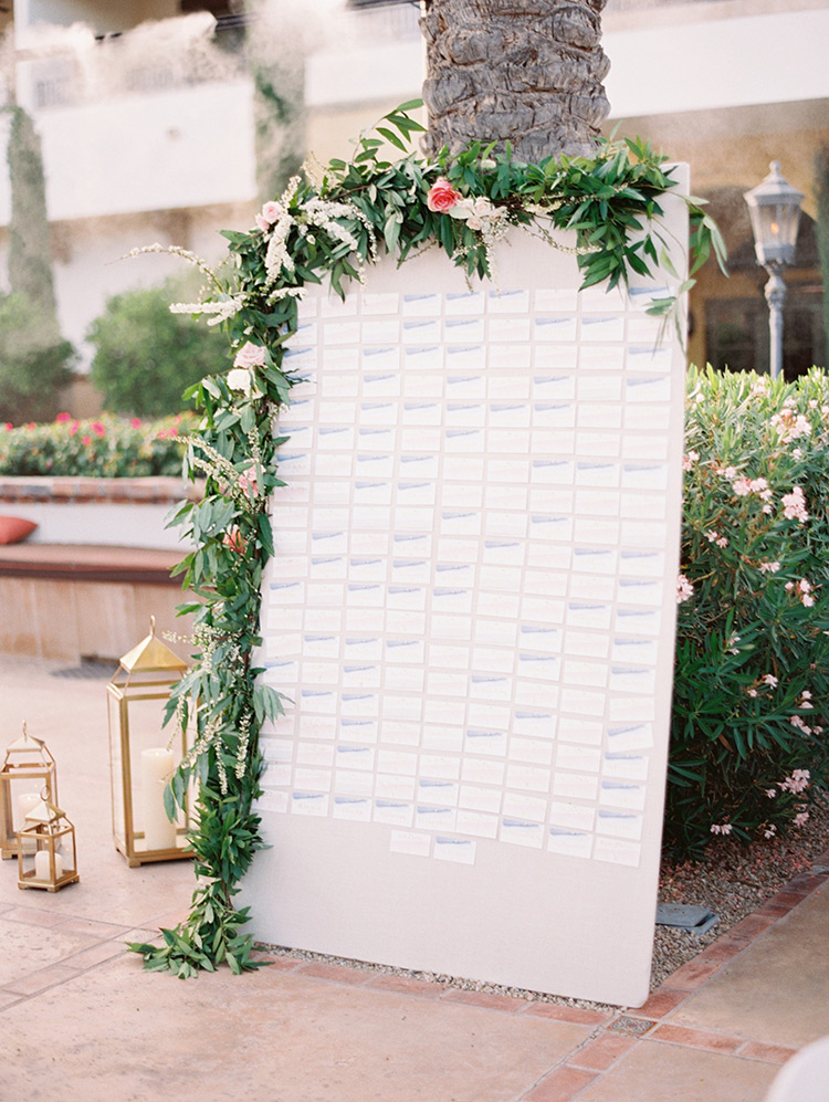 escort card display draped with a flowering garland