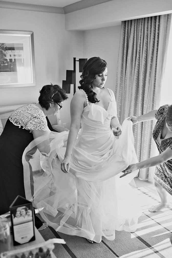 helping the bride into her dress