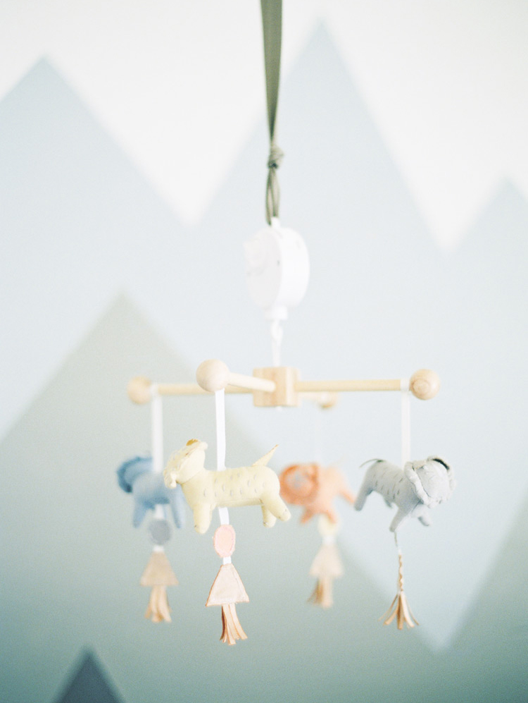 modern nursery with plush animal mobile