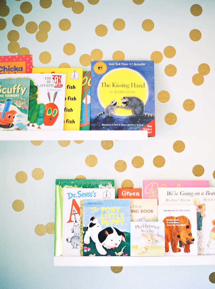 Polka dot walls and display bookshelves in a charming nursery