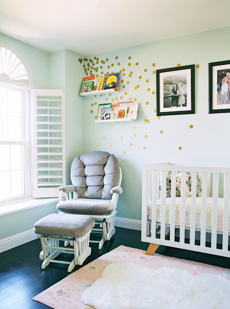 Charming nursery with custom polka dots walls, display bookshelves, and family portraits